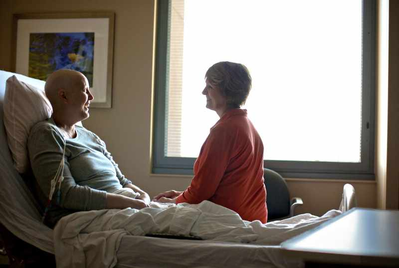 cancer patient in hospital bed talking with friendly visitor