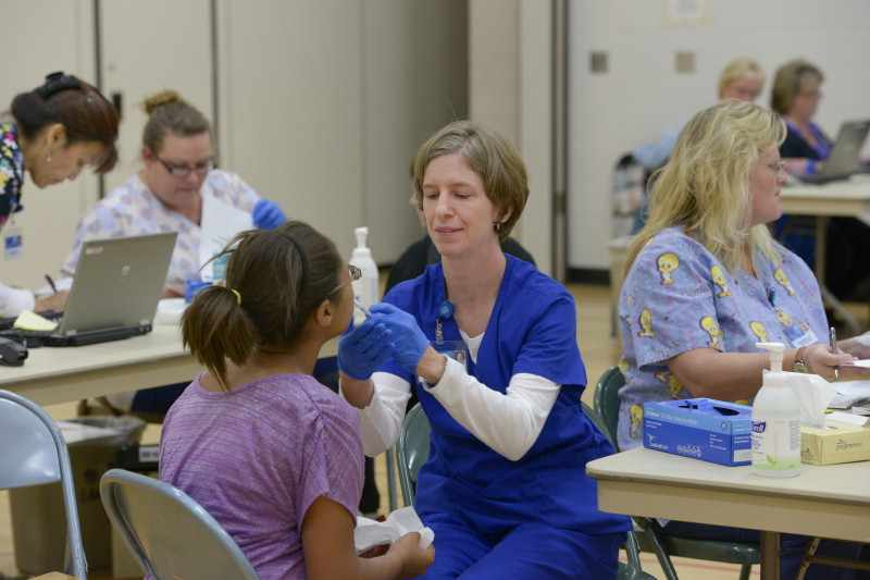young girl in school clinic getting flu vaccination, nasal spray