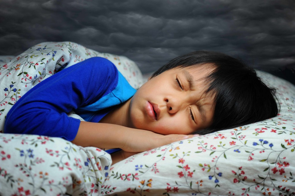 little girl sleeping, looking worried or frightened like she's having a nightmare dream