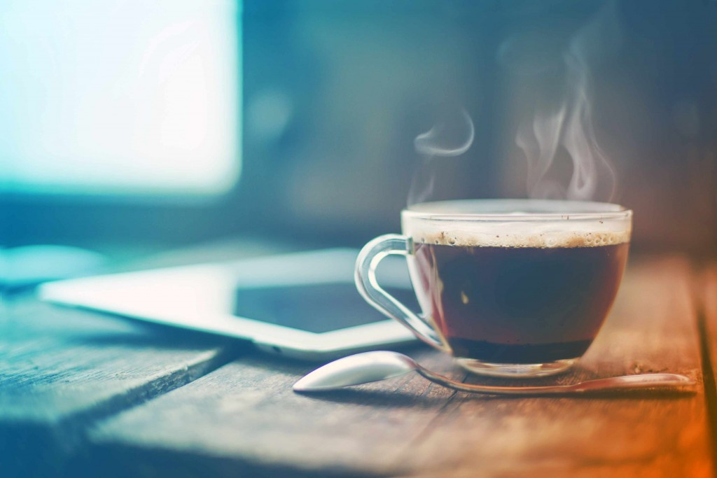 steaming cup of coffee on table with iPad