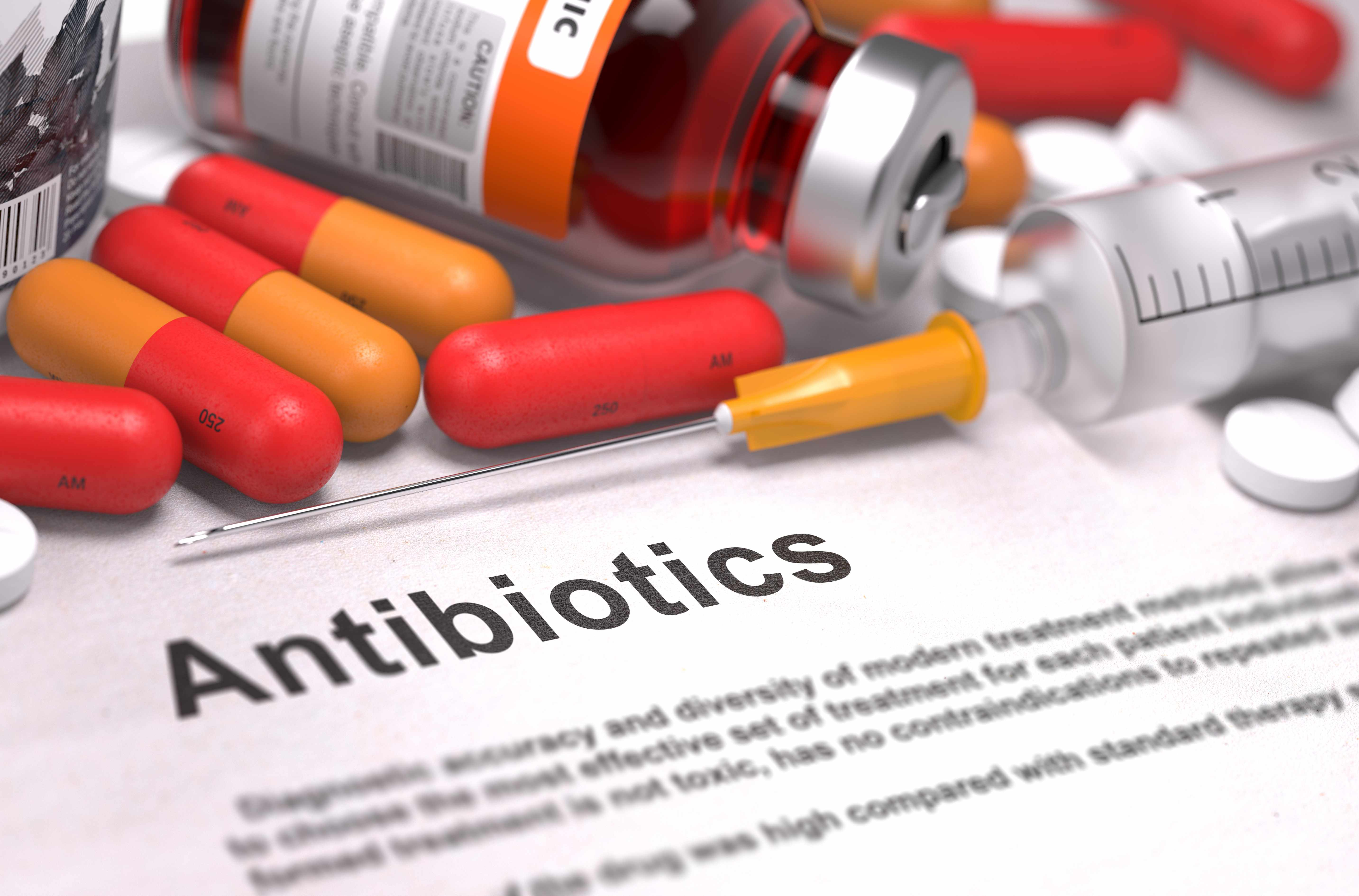 pills, medicine, antibiotic, syringe with the the word antibiotic on a piece of paper