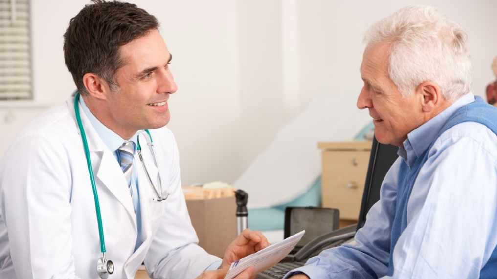 male doctor talking with elderly male patient 16 x 9