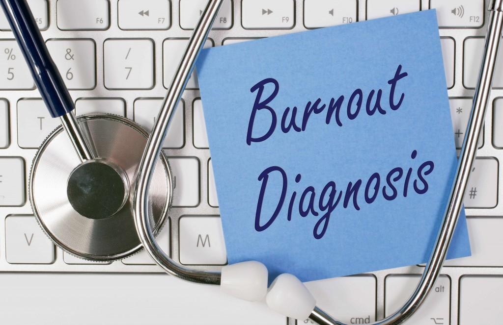 """Una nota que dice """"diagnóstico de desgaste profesional"""" aparece sobre el teclado junto a un estetoscopio"""