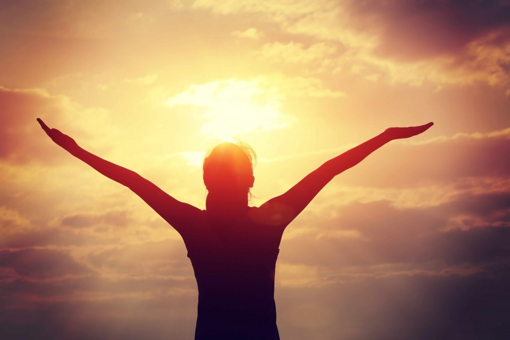 woman looking at sky and sun with open arms, thankful, grateful