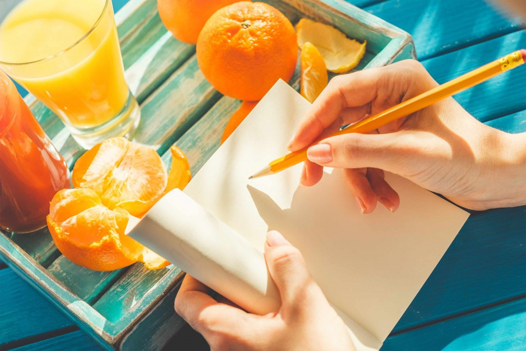 a woman's hand on a journal near a tray of oranges and juice
