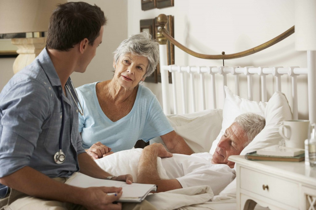 patient in bed and physician, doctor sitting with patient and family member
