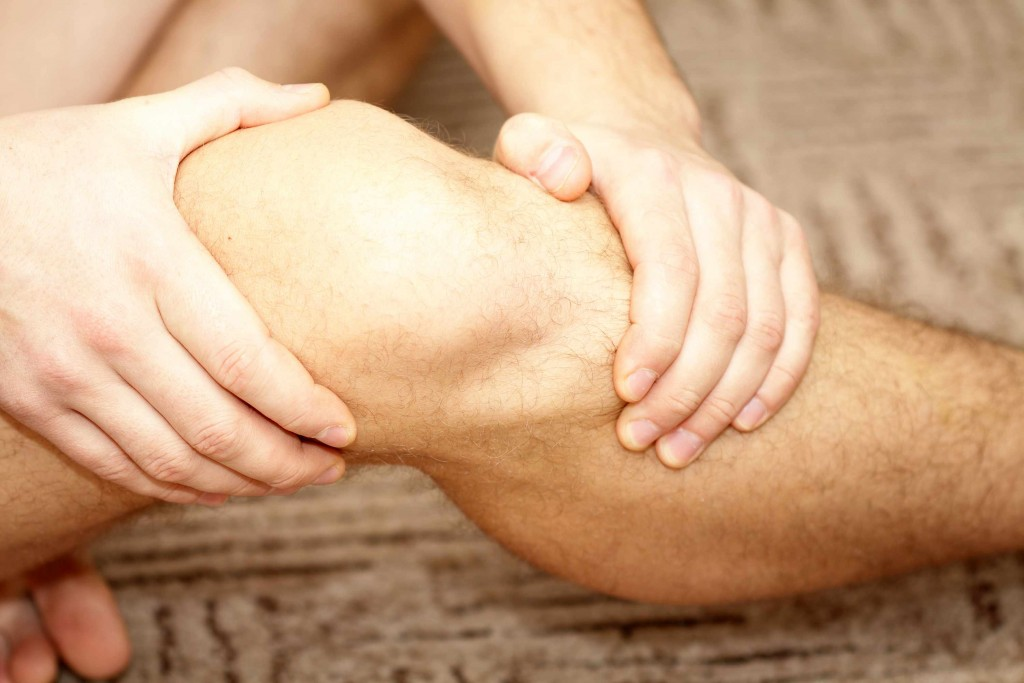 a close-up of a man's knee, with his hands gripping on either side above and below, holding it as though in pain