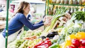 woman at a farmers market choosing vegetables