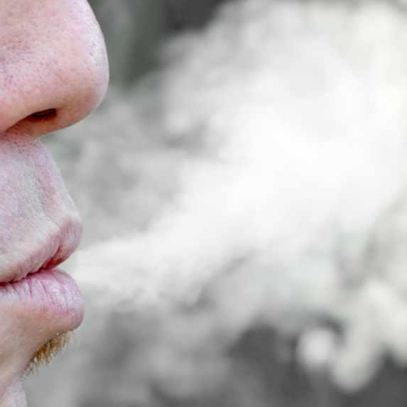 man exhaling cigarette smoke