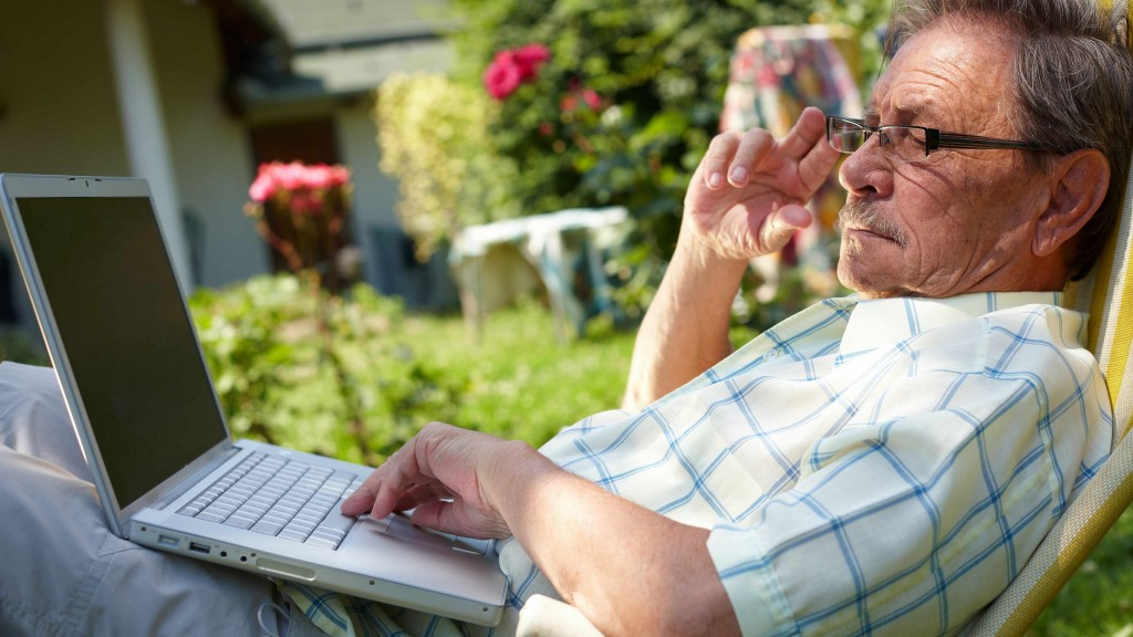 elderly man wearing glasses reading, looking at laptop computer