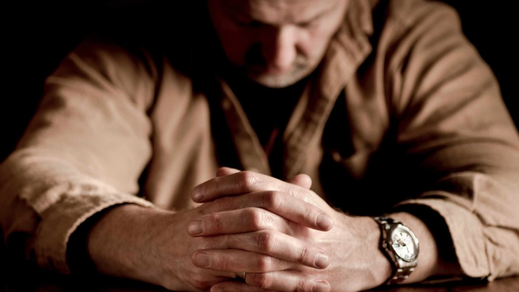 man sad, with grief, folding hands and praying