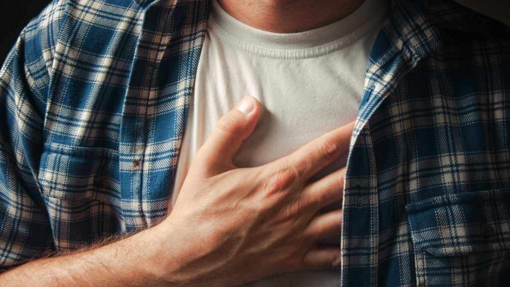 man with hand on chest