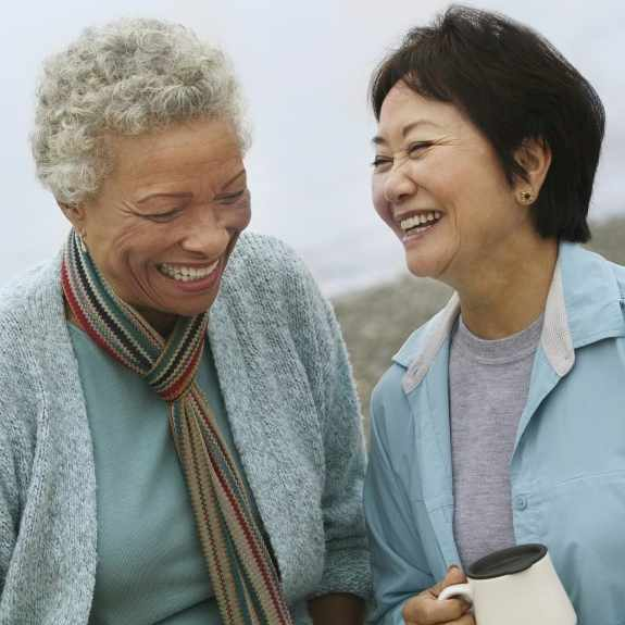 middle-aged women, friends laughing and comforting each other on a walk