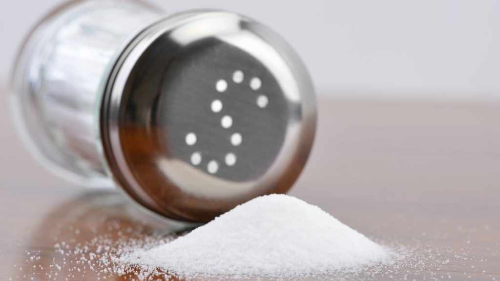 a salt shaker on its side next to a mound of salt