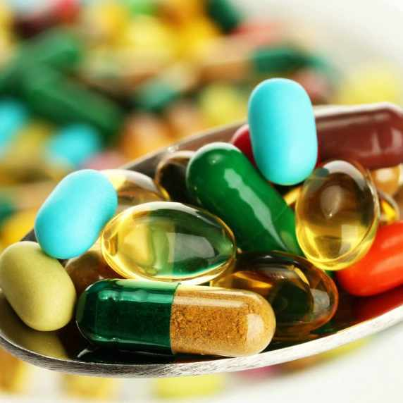 spoonful of different pills and medication tablets