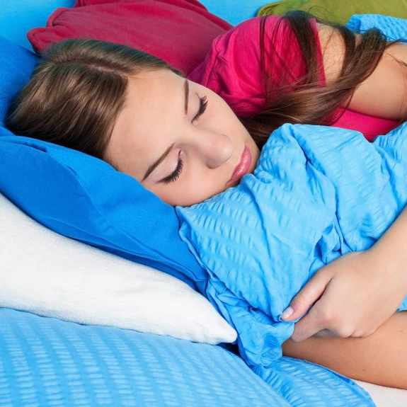 teenage girl sleeping in bed with blue covers