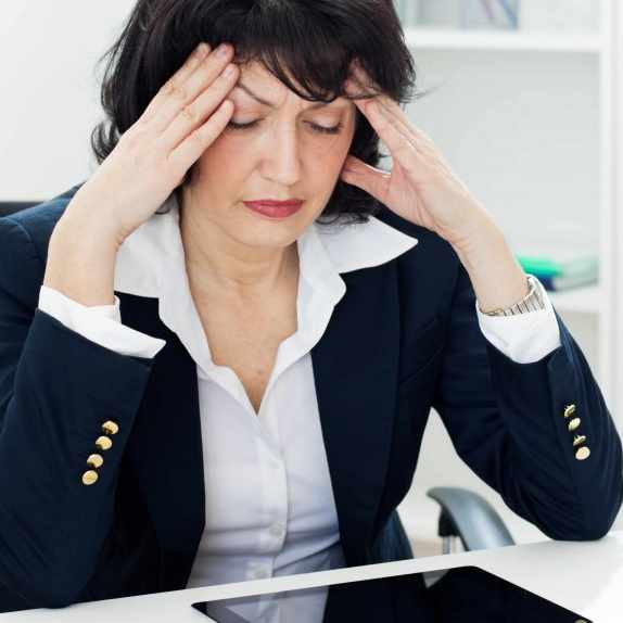middle aged business woman at desk with headache