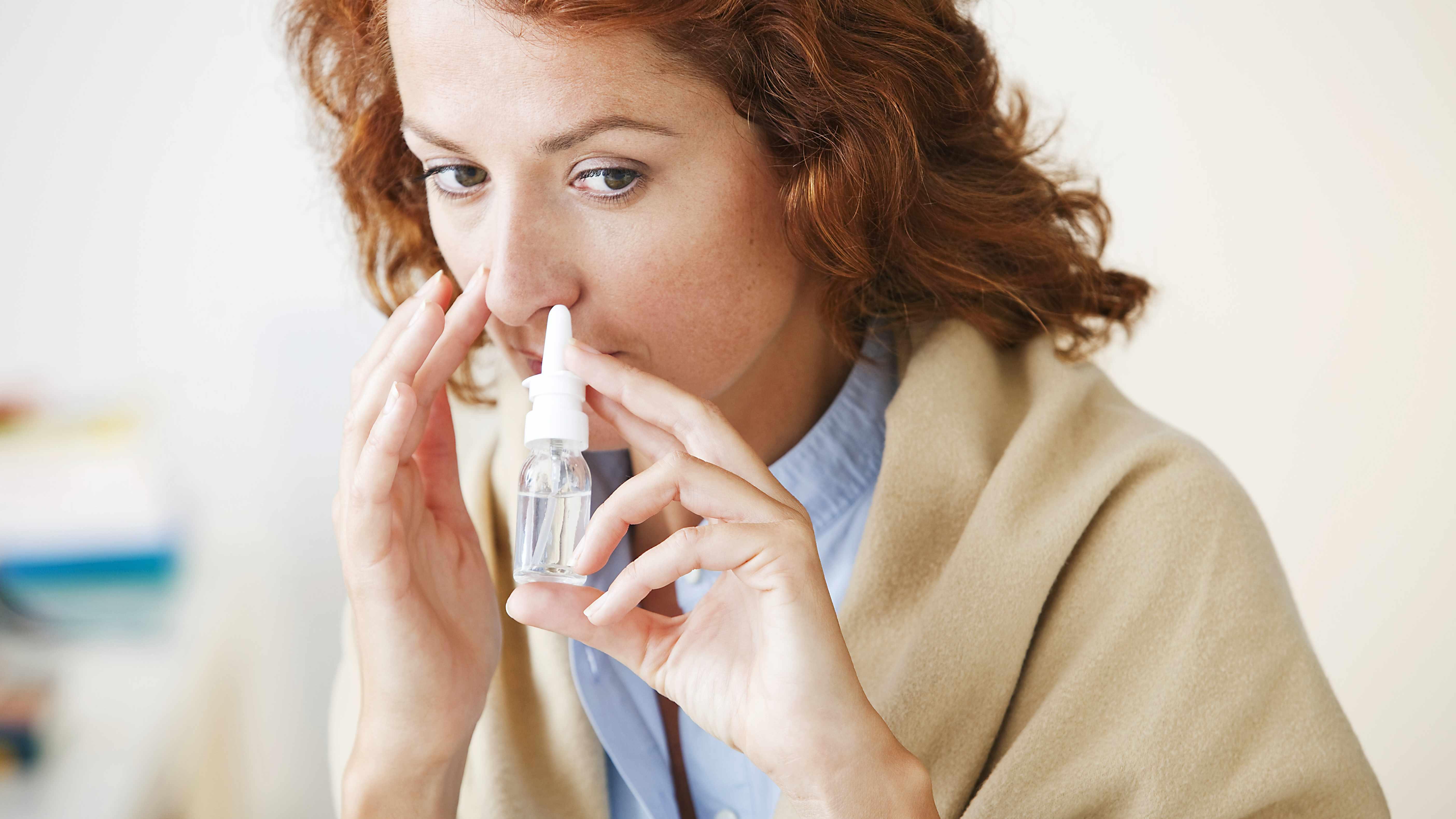 woman using decongestant nasal spray