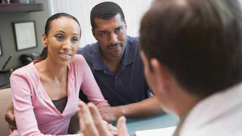 young couple conversing with a fertility specialist