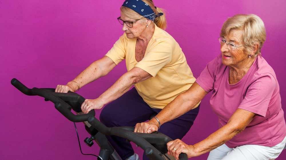 Imagen de dos ancianas en el gimnasio, ejercitando las piernas en bicicletas estacionarias