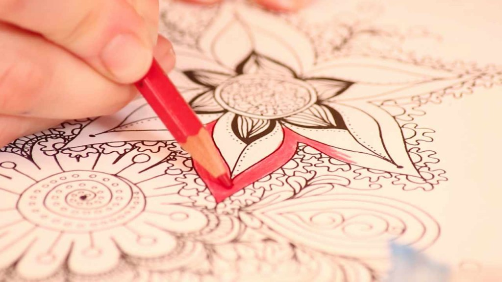 person coloring an image with a red pencil