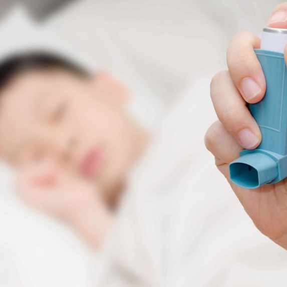 young child sleeping, adult hand holding an inhaler for asthma