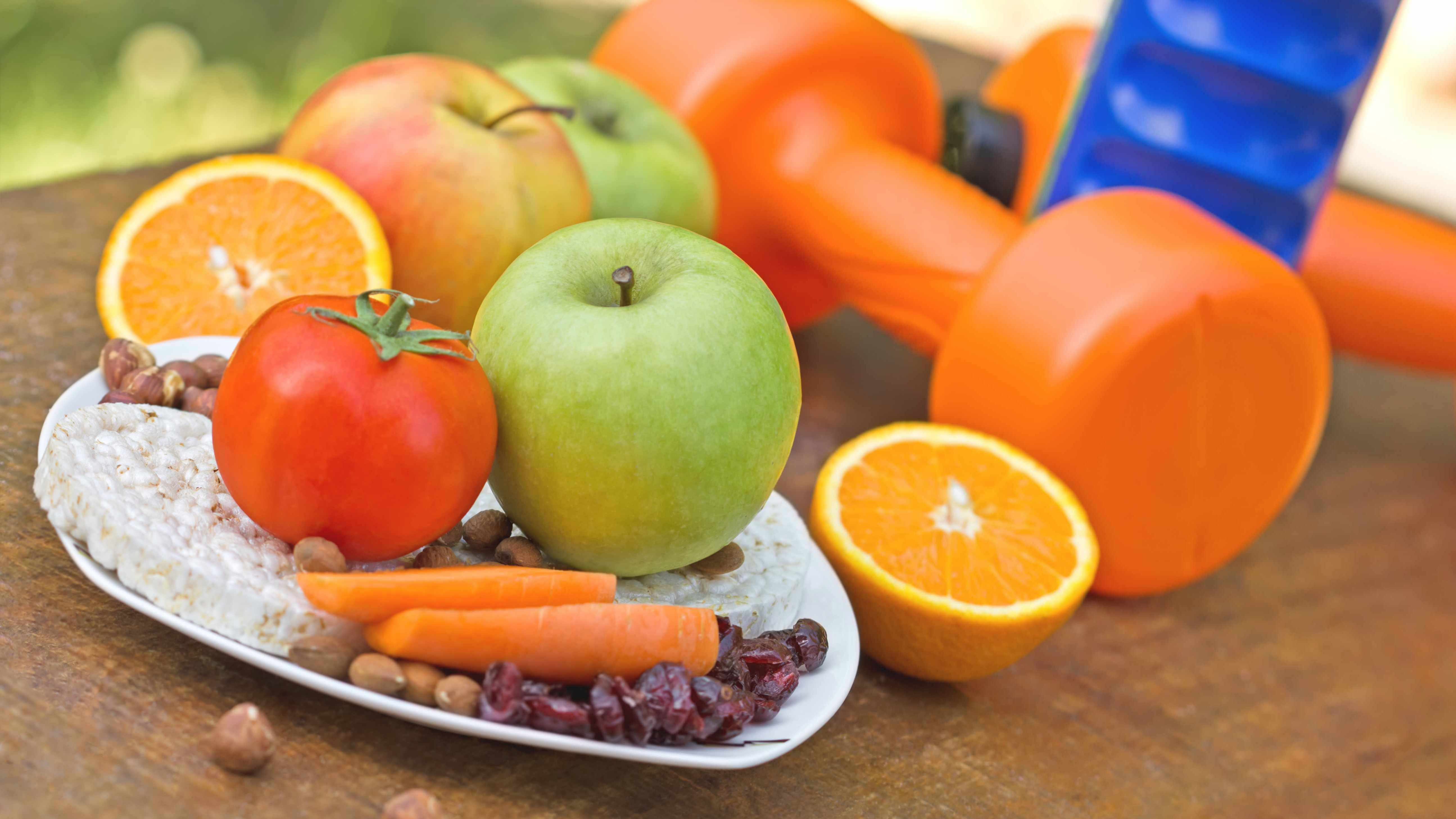 image of fruits, vegetables and hand weights representing healthy lifestyle