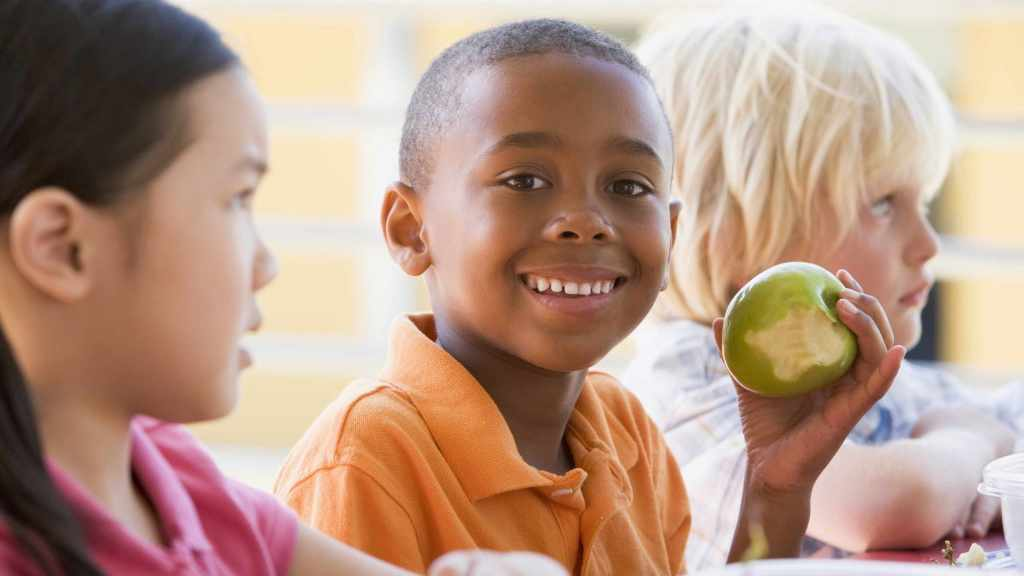 kid at lunch table, eating an apple