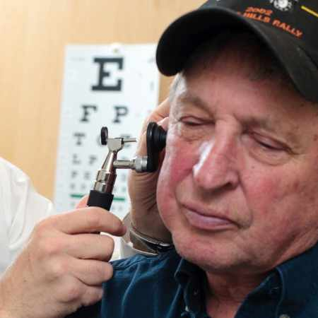 male patient with doctor checking for ear infection