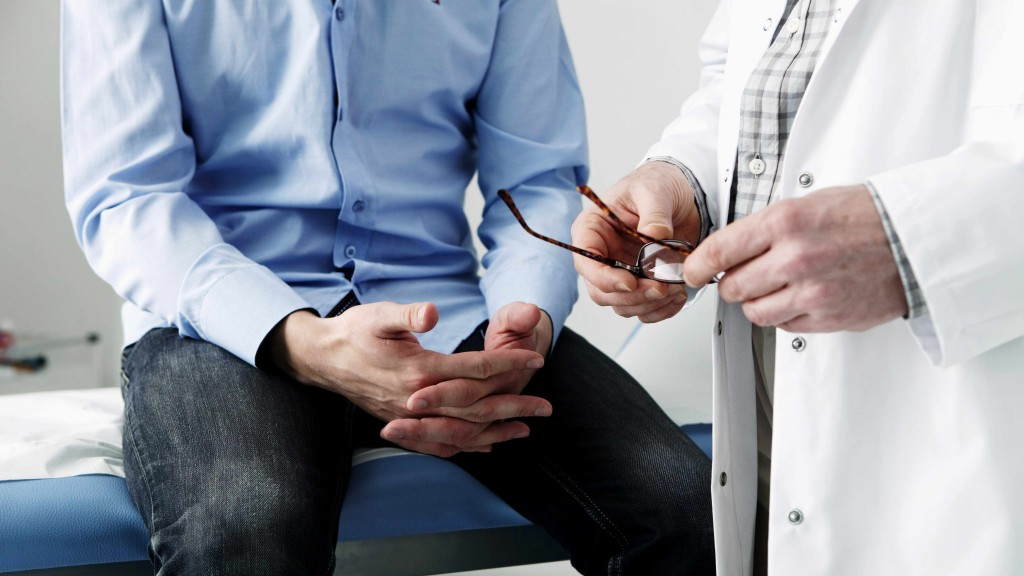 man in hospital exam room consulting with medical staff