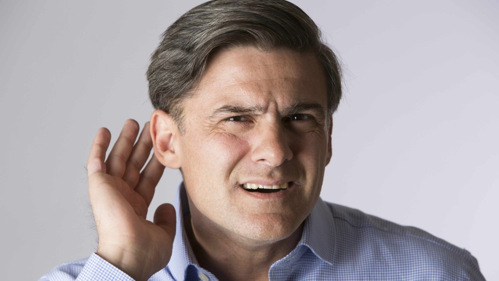 a man trying to listen, cupping his ear because of hearing loss