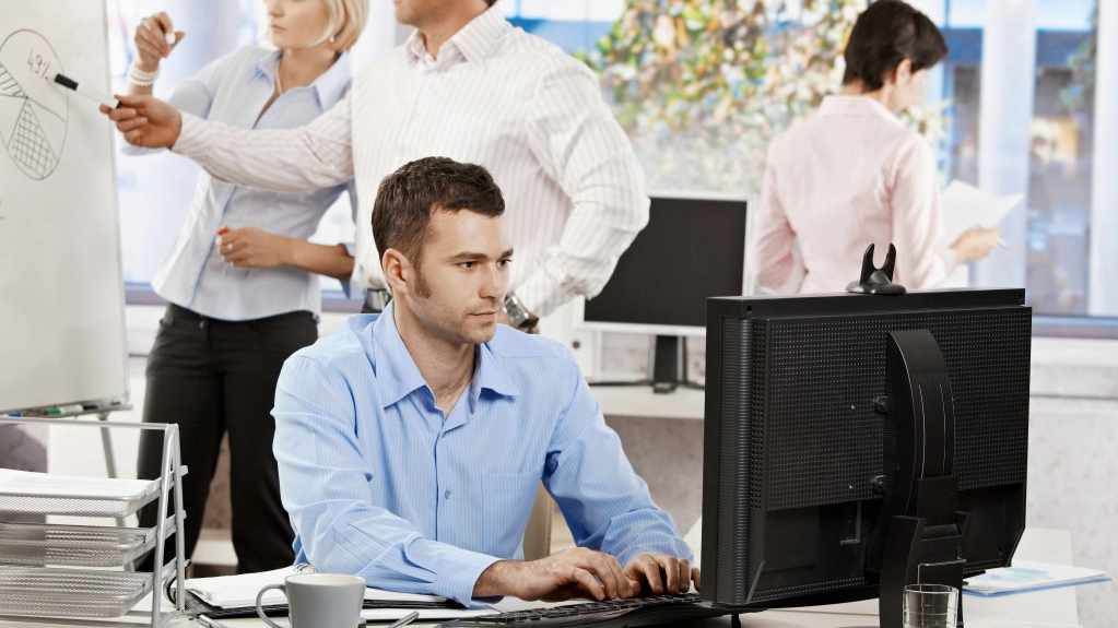 man sitting at on office computer and other people standing, working behind him