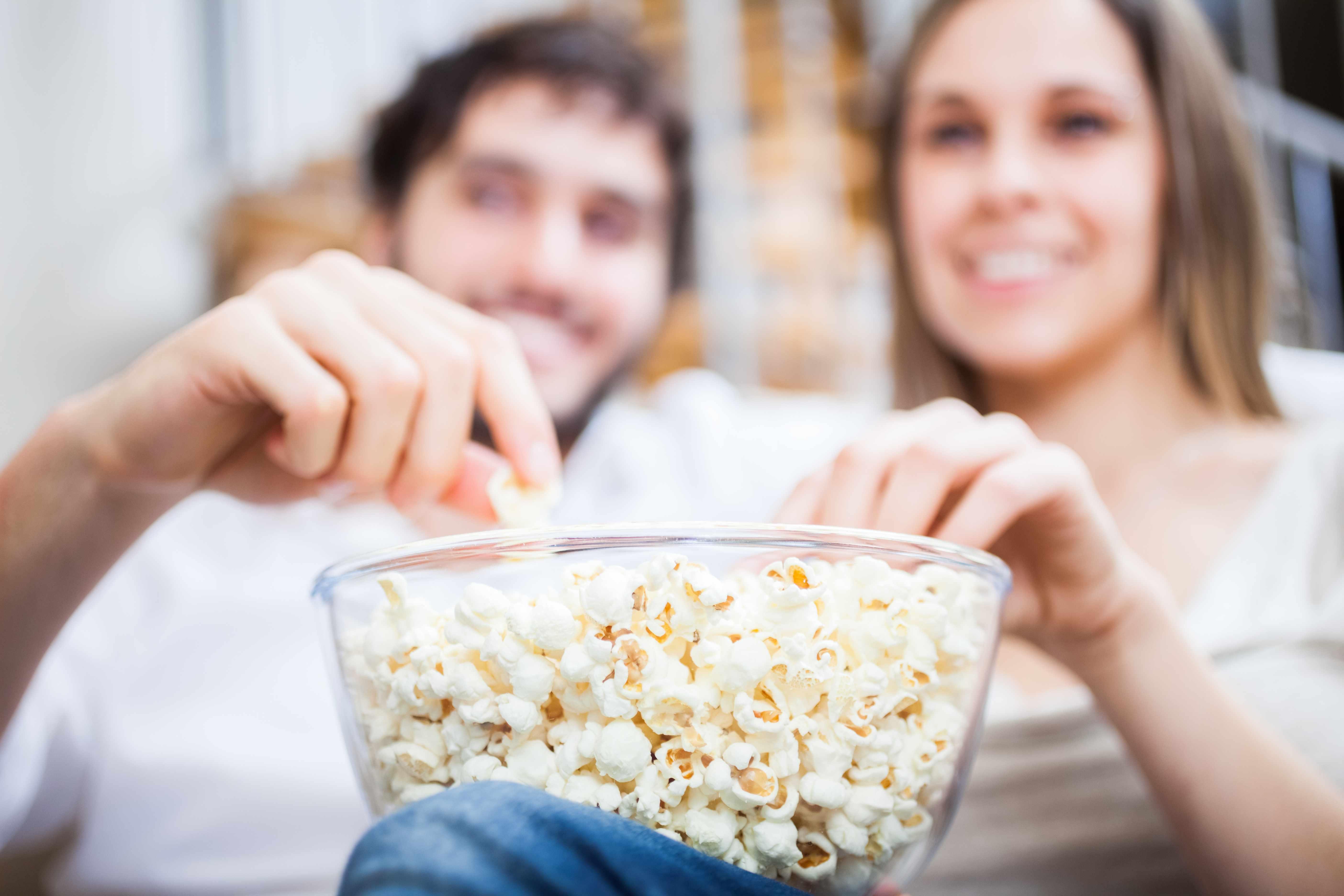 couple enjoying eating a bowl of popcorn