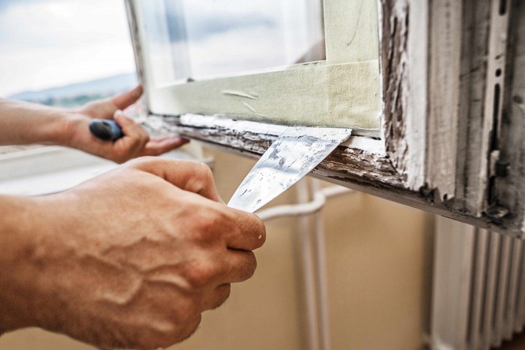 man repairing painted window frame, lead paint