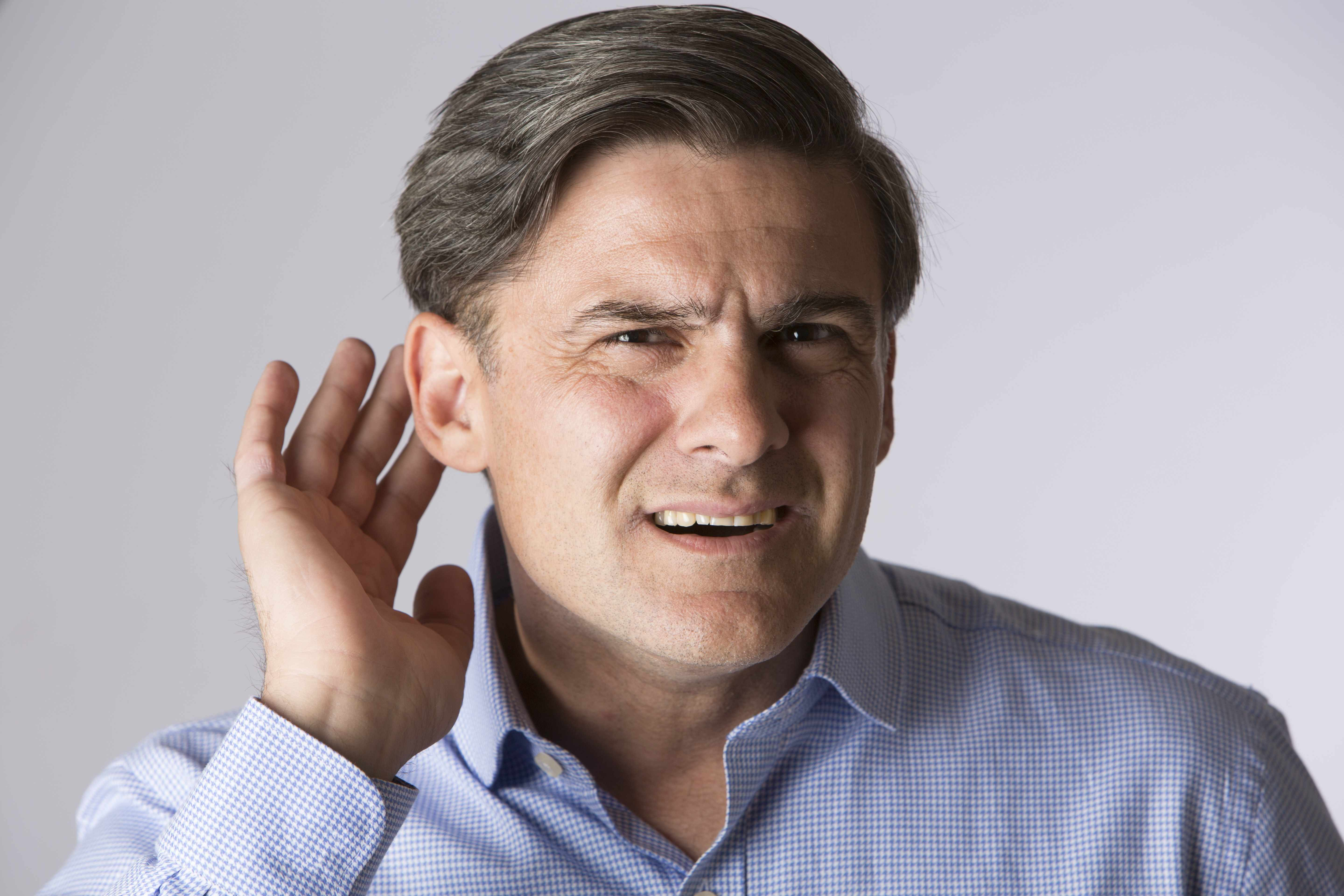 man trying to listen, cupping his ear because of hearing loss