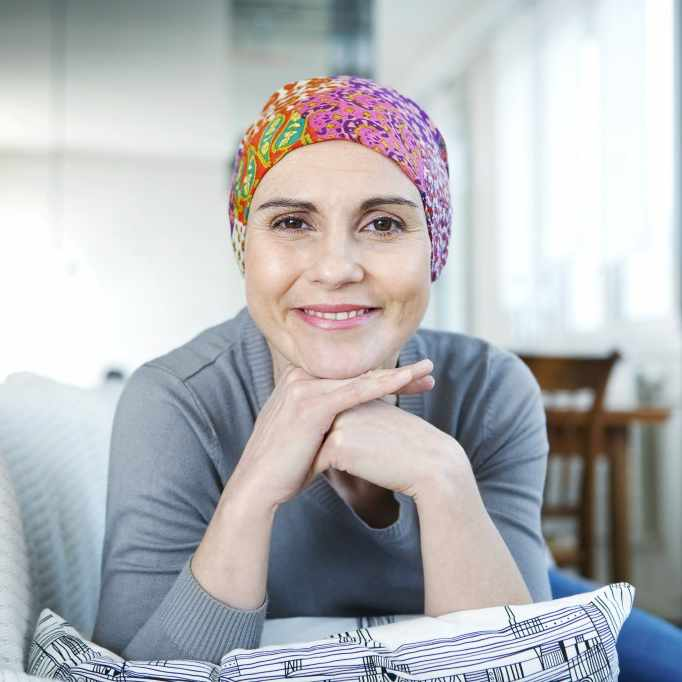 woman cancer survivor with scarf, smiling