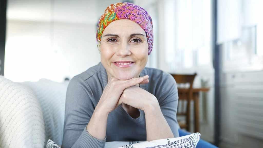 mujer sobreviviente de cáncer con bufanda, sonriendo