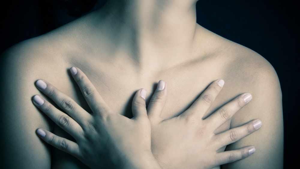 Una mujer se cubre los senos