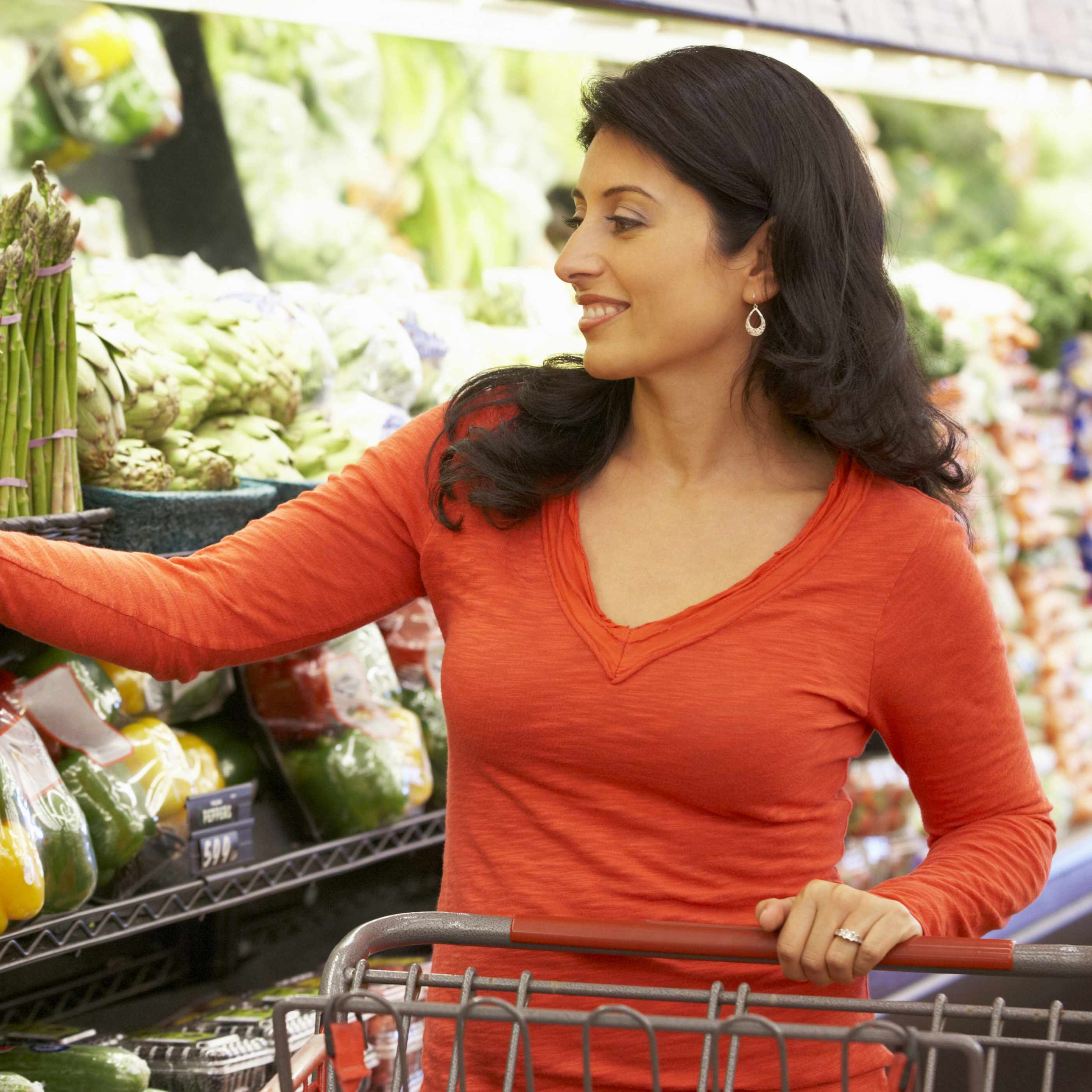 woman shopping in grocery store for healthy food, vegetables