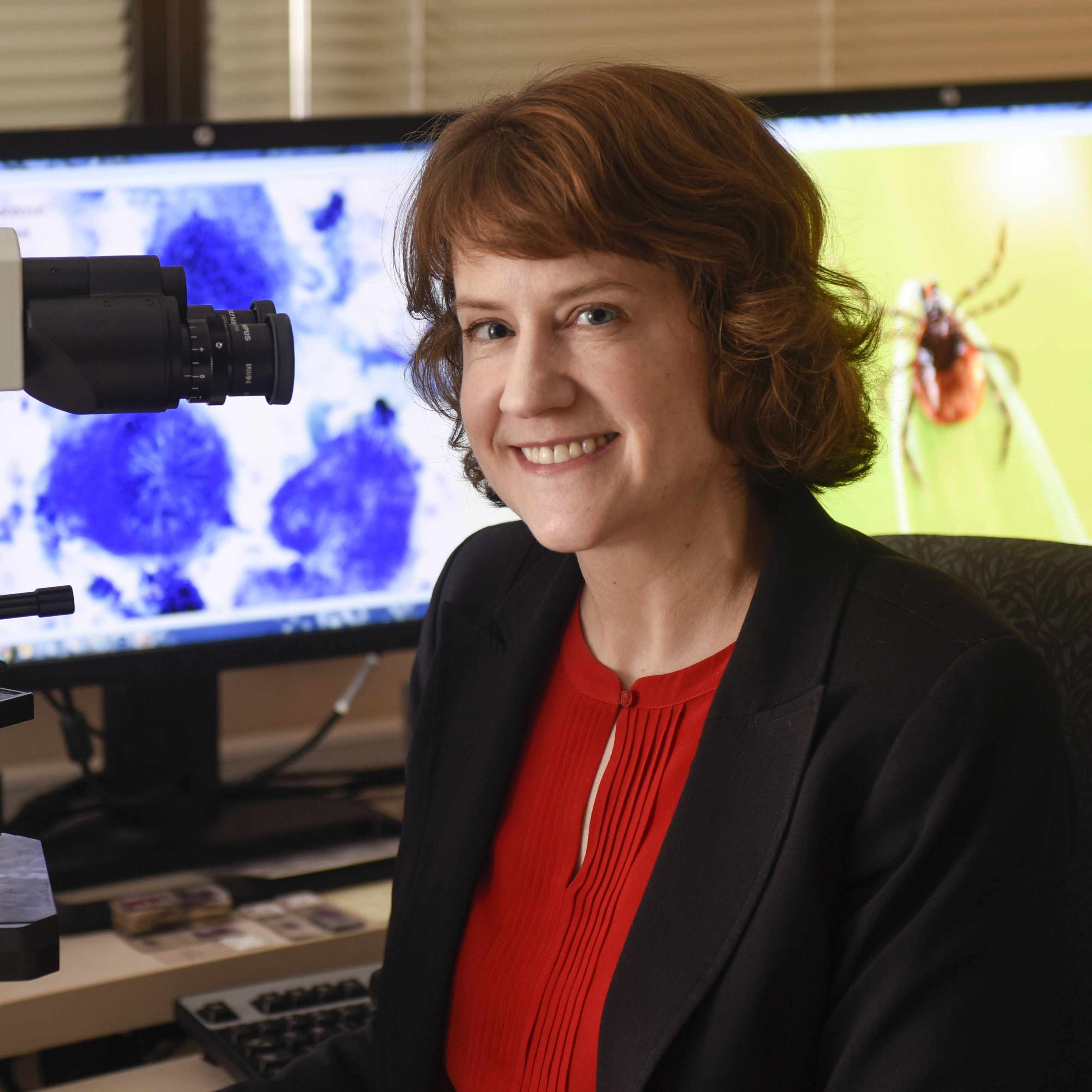 Dr. Bobbi Pritt in a lab, sitting at a microscope, with computer monitors in the background