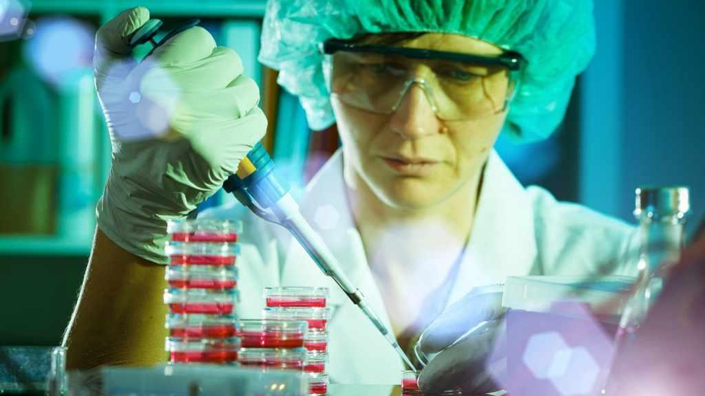 Acercamiento de un empleado que trabaja en investigación con los equipos del laboratorio, usando guantes y otras protecciones
