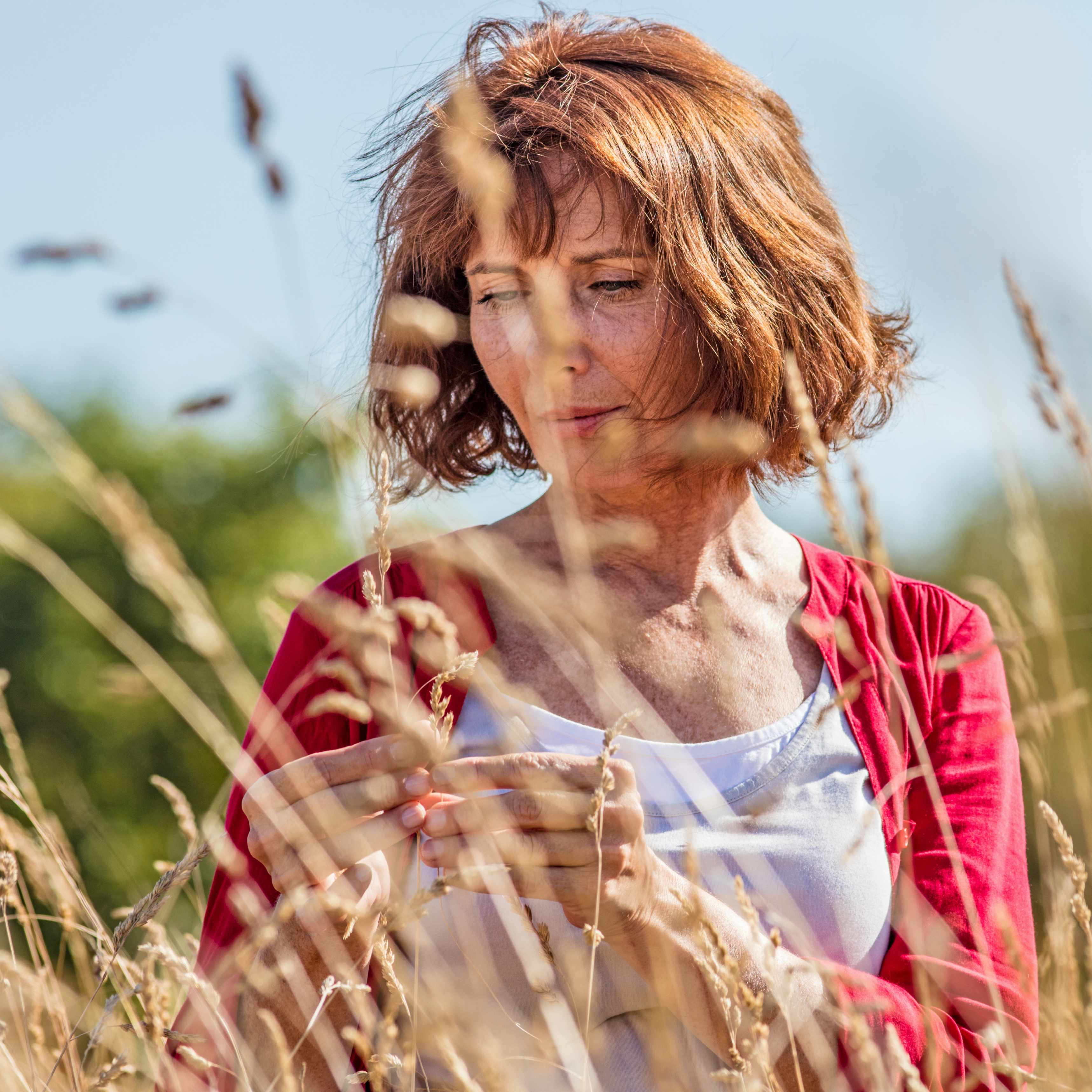 a middle-aged woman outside in a field, looking serious and thinking