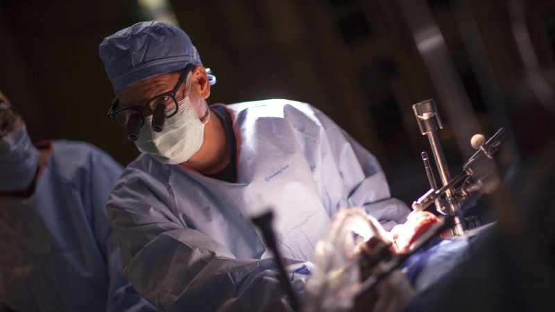 a surgeon in operating room performing a lung transplant
