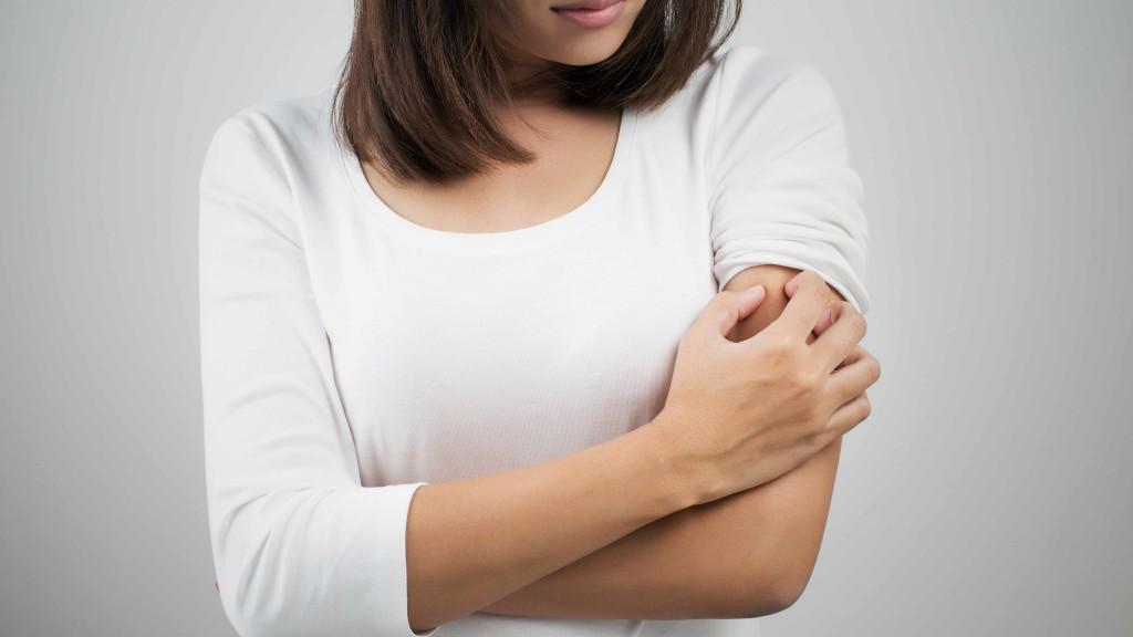 una mujer rascándose una picazón en el brazo