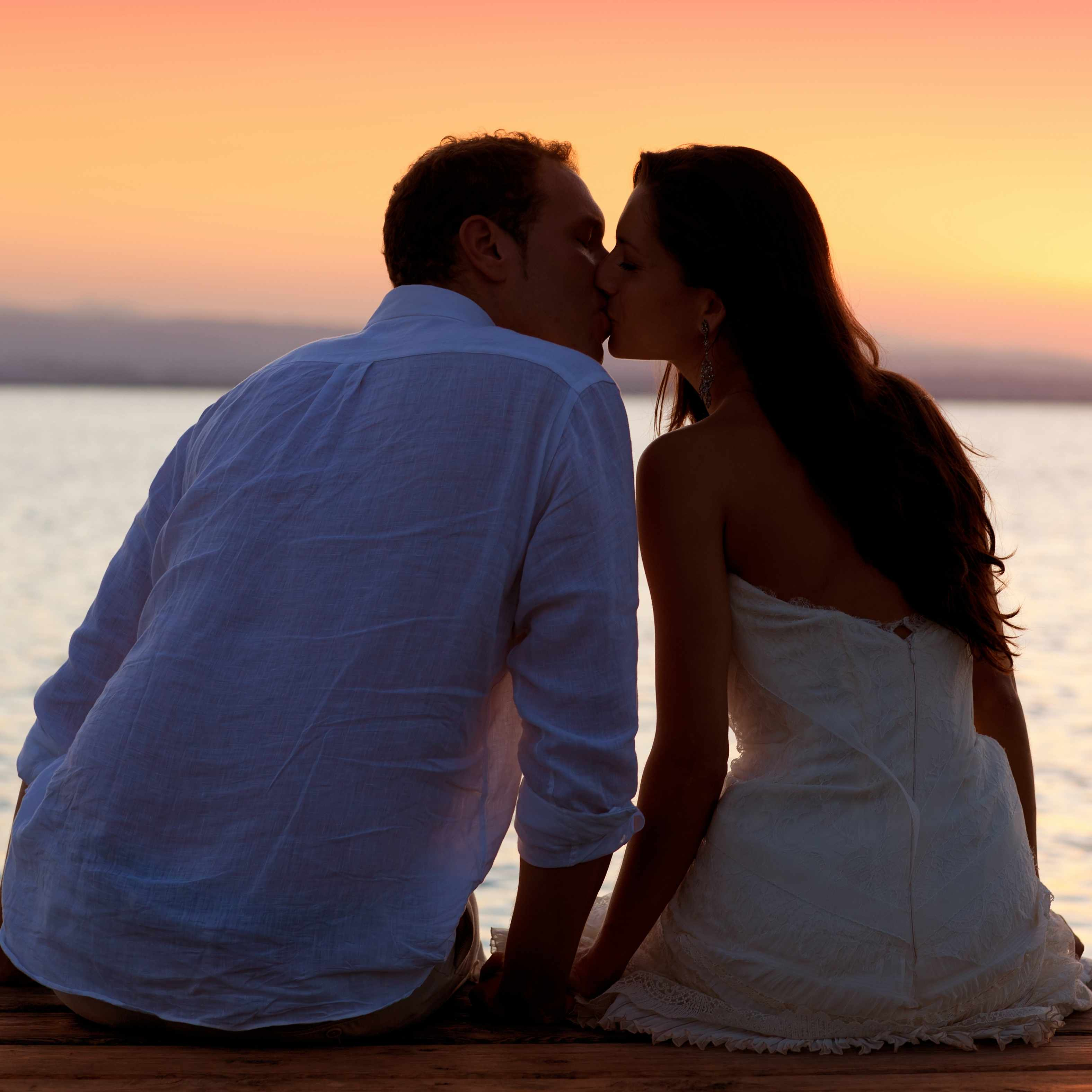 a young man and woman, couple sitting on boat dock kissing with sunset in background