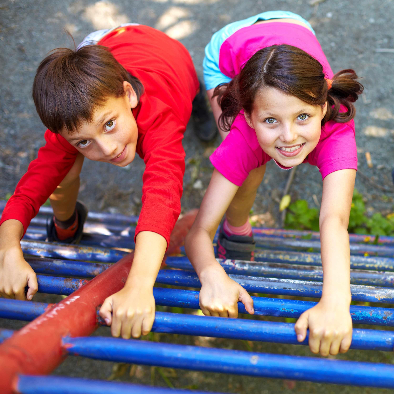 children smiling, climbing on the playground