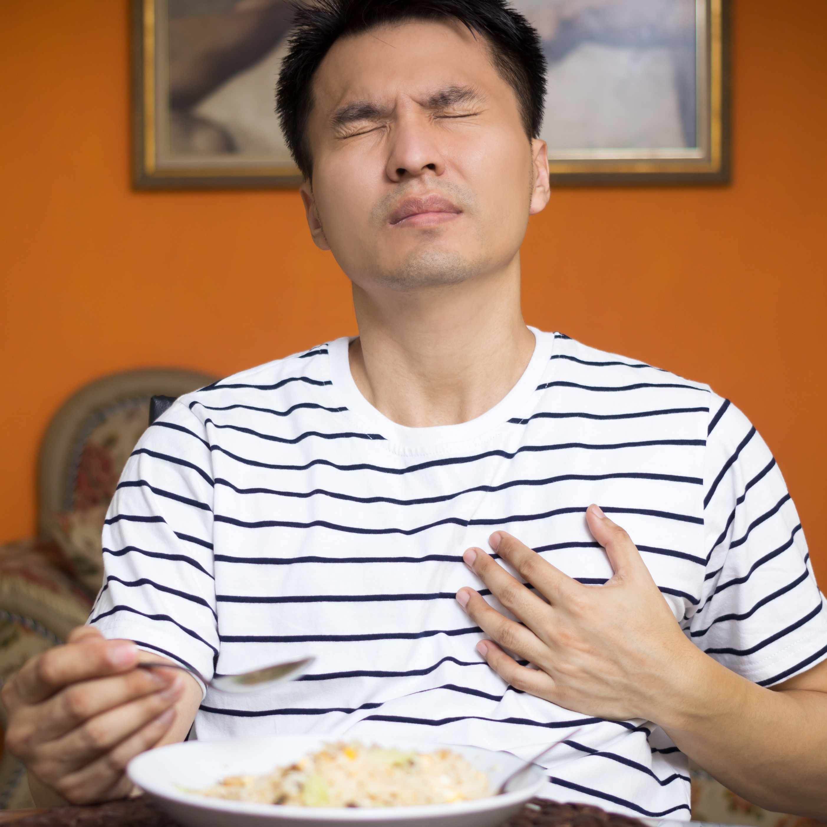 A man experiencing pain while eating food