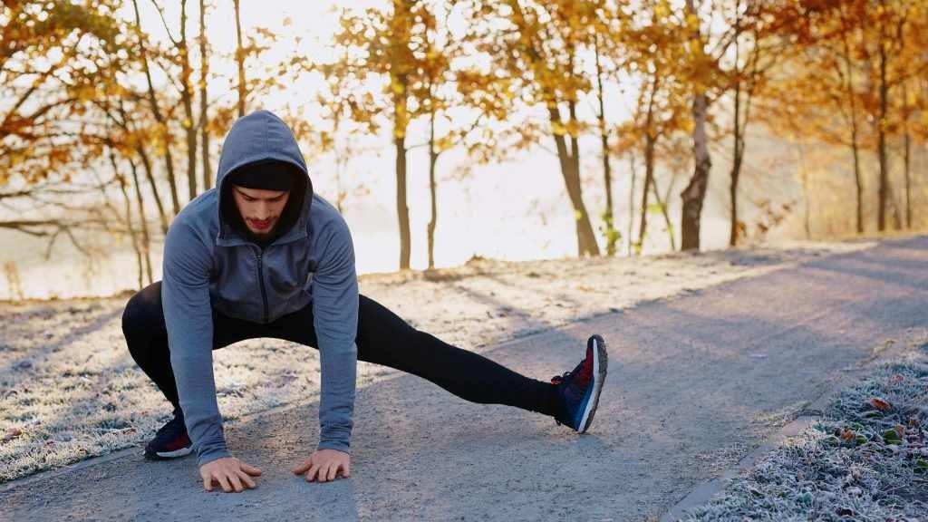 un hombre se estira antes de hacer ejercicio y correr