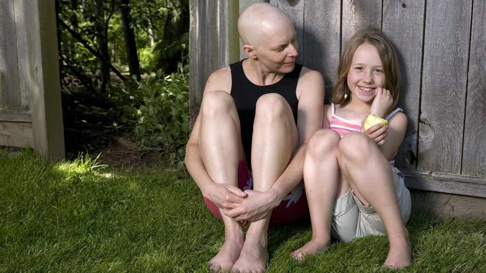 Una madre que lucha contra el cáncer de mama sentada afuera con su hija pequeña junto a una cerca de madera