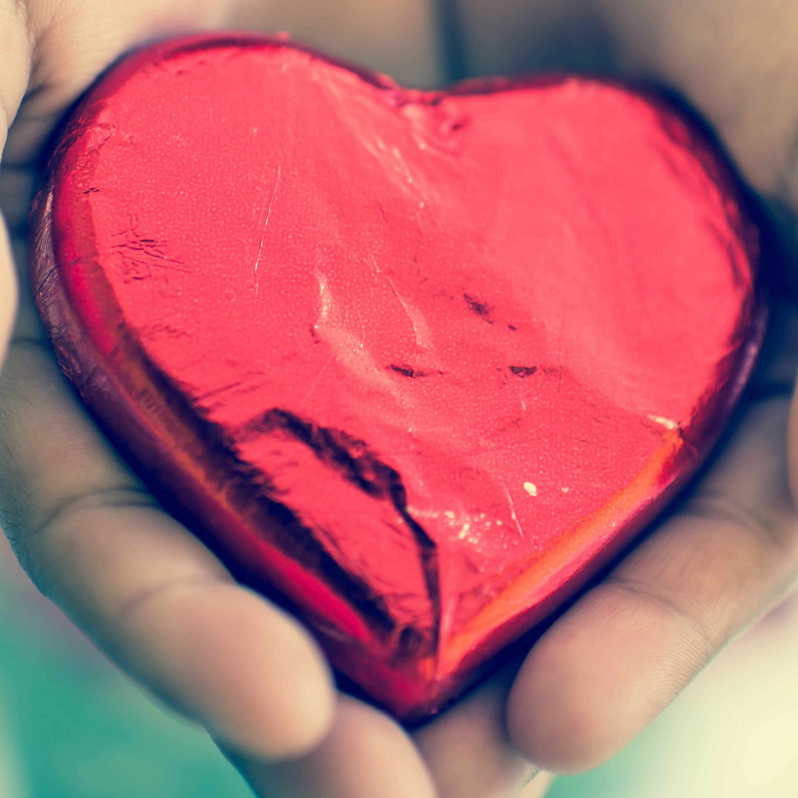 person holding chocolate heart wrapped in red paper